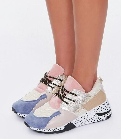 model wearing the purple, tan, cream, pink, metallic, and black and white spot lace up sneakers
