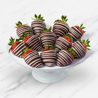 Several strawberries covered in milk chocolate and white chocolate stripes