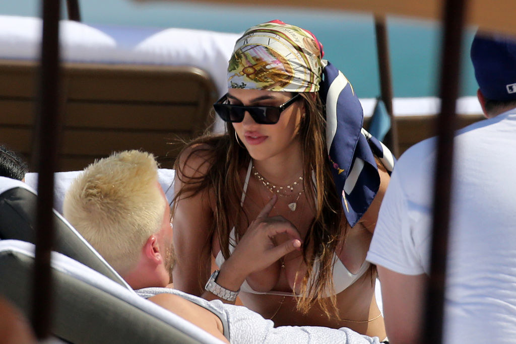 Amelia leans over Scott as he lays on a lounger at the beach