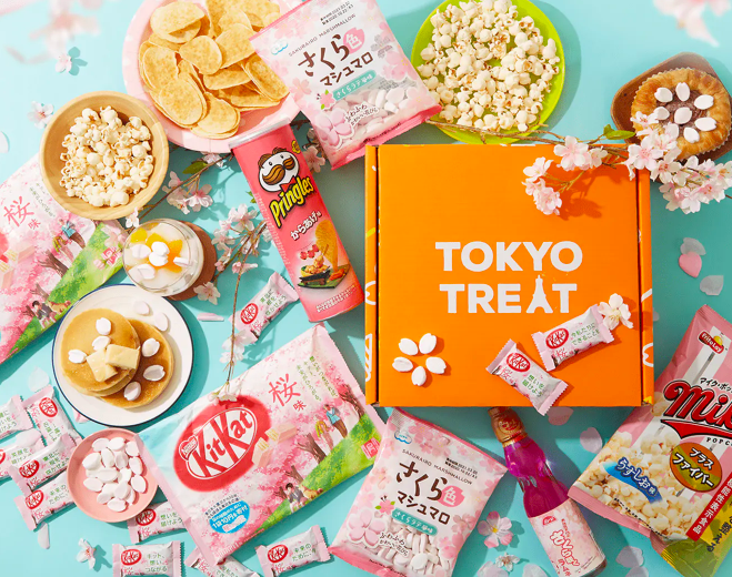 Several different candies and treats beside a TokyoTreat box