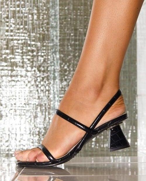 model wearing croc effect sandals with low sculptural heel