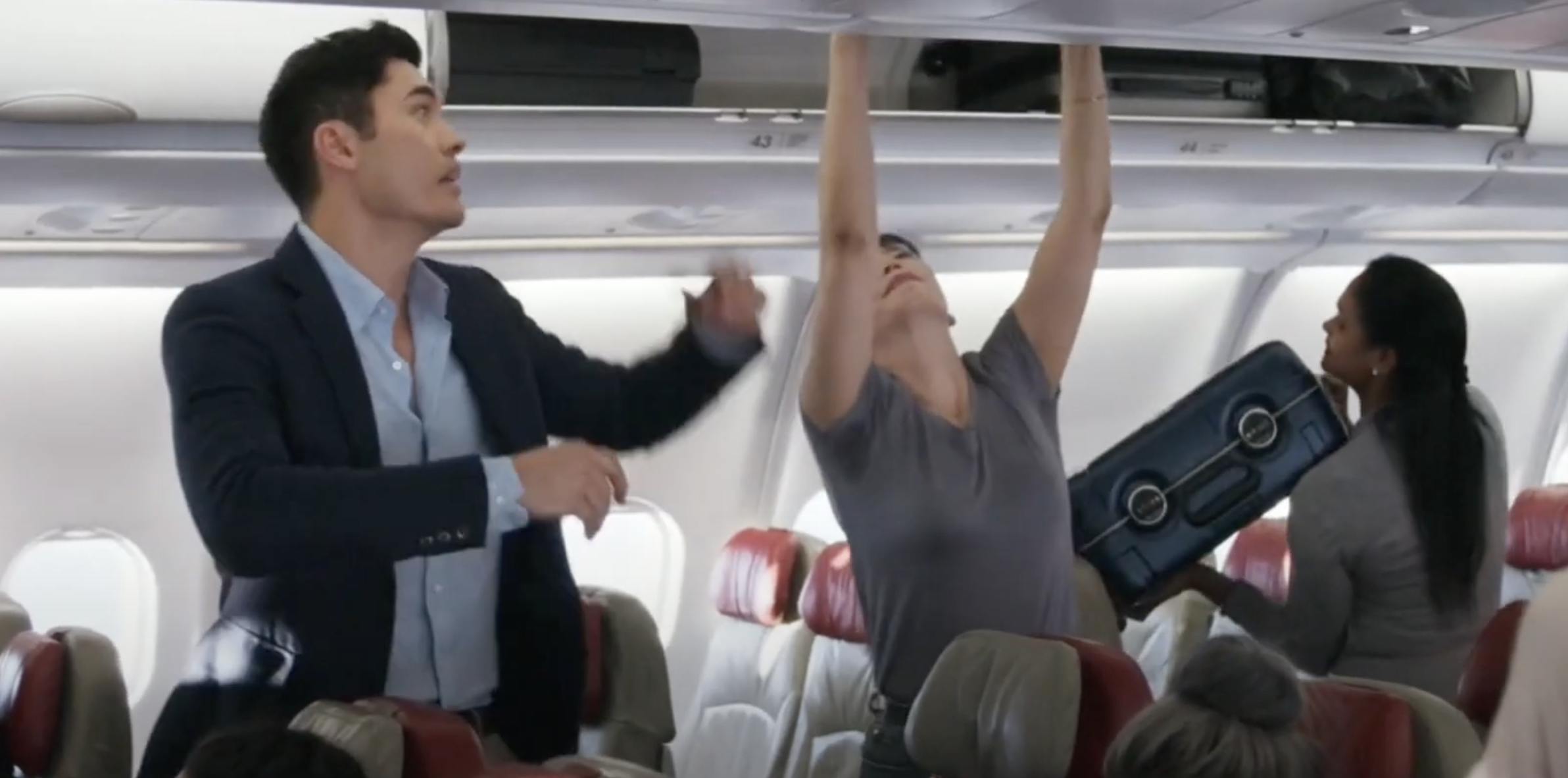"""Nick helping a woman lift her bag in """"Crazy Rich Asians"""""""