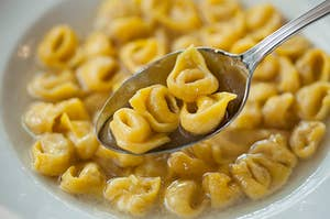A spoon full of tortellini over a bowl of tortellini