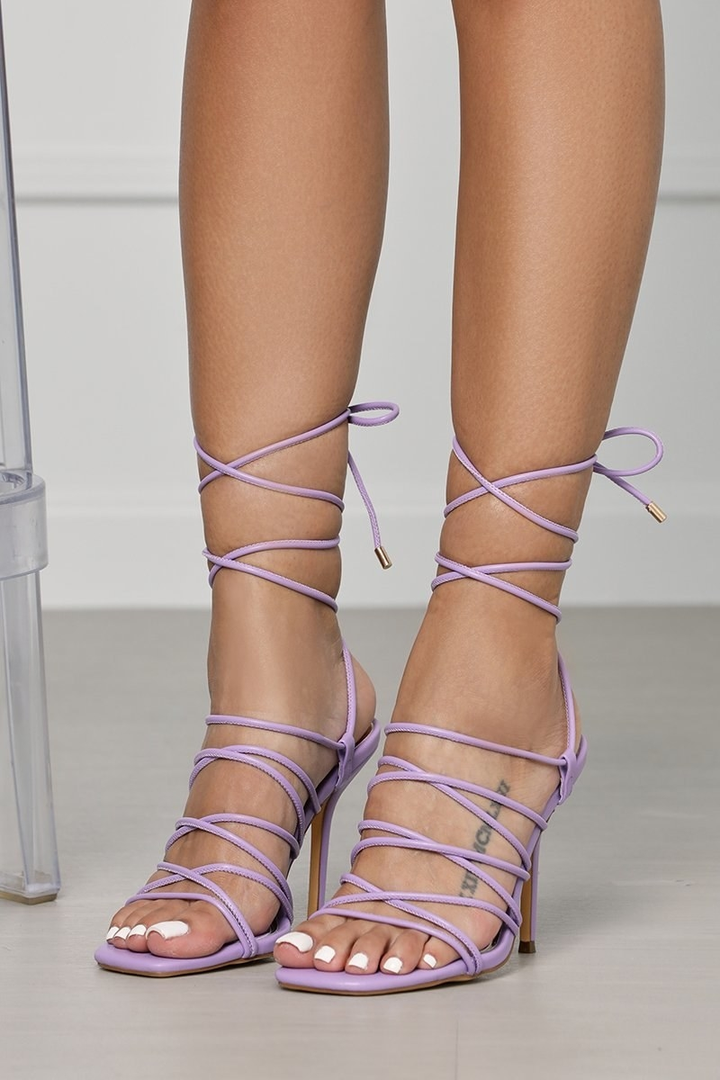 model wearing the 4-inch heel strappy sandals with the straps tied around the calves