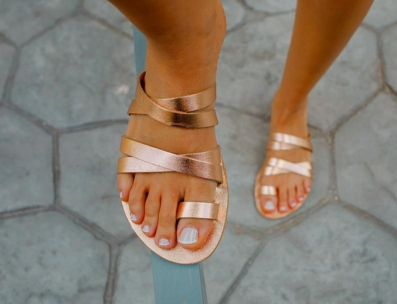 model wearing the strappy rose gold flat sandals