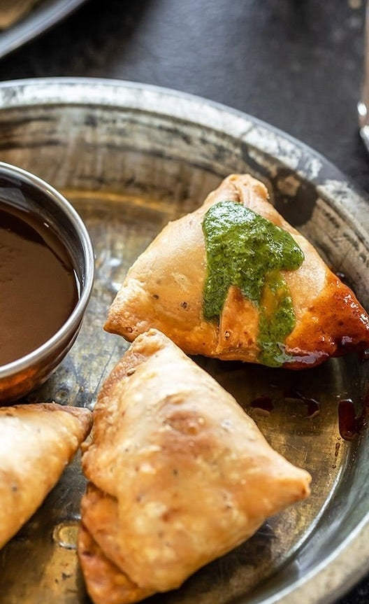 Fried samosas topped with green sauce.