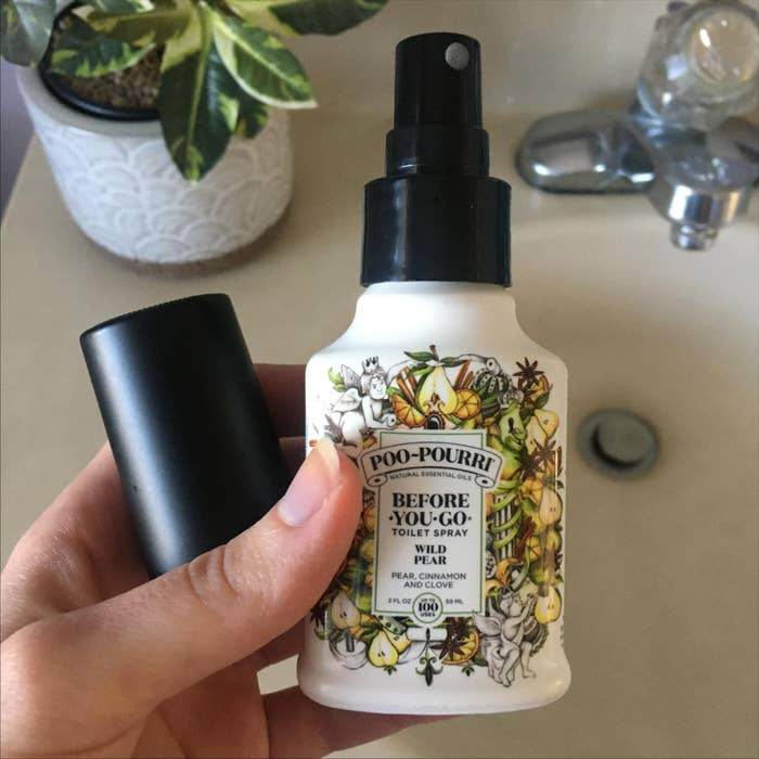 Reviewer holding a spray bottle of wild pear poo-pourri