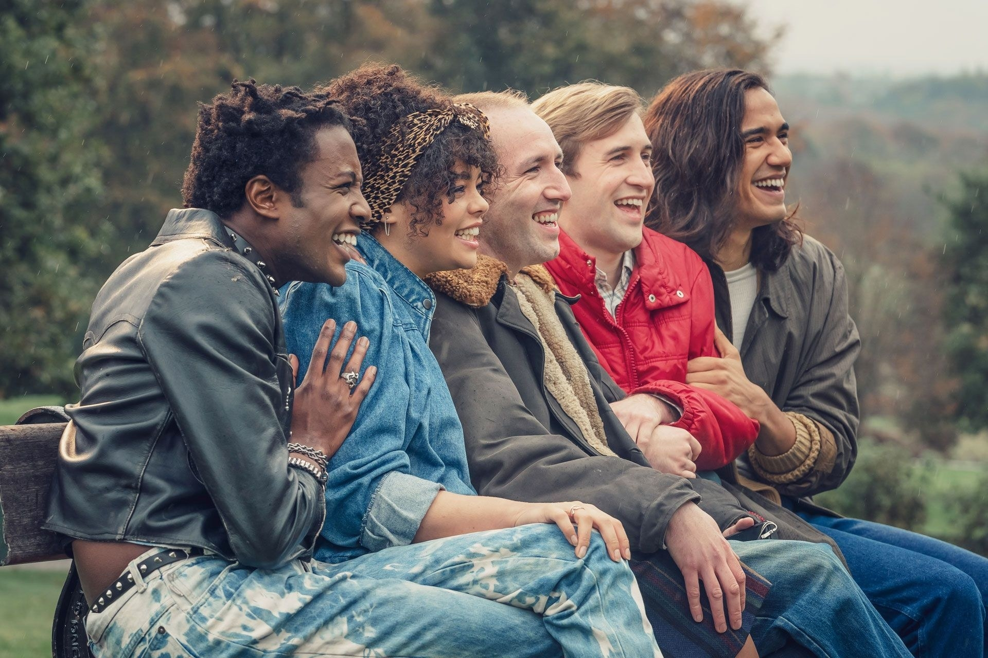 Five friends sit on a park bench and laugh