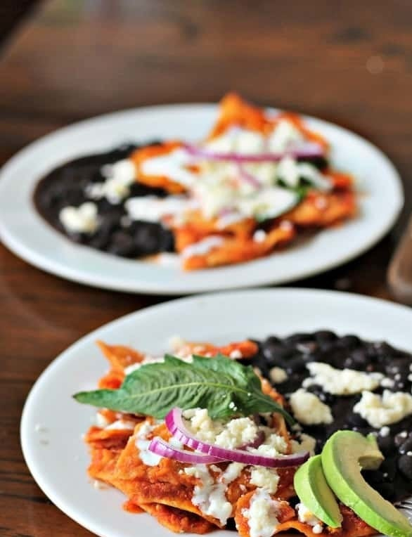 Chilaquiles rojo topped with cheese, avocado, onion, and plated with black beans.