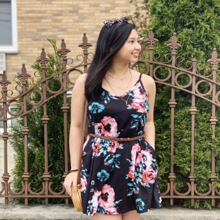 A person wearing a black floral dress