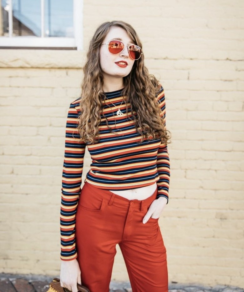 A person wearing a multi-colored striped cropped long-sleeve top and red pants