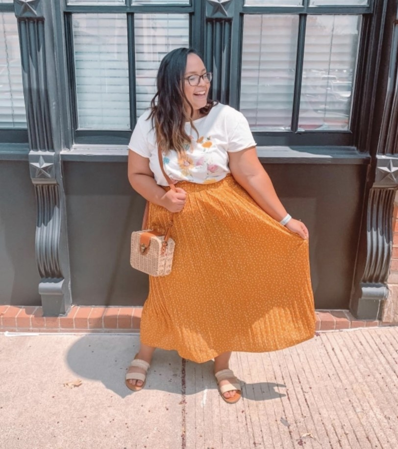 A person wearing a bright orange maxi skirt and a white top