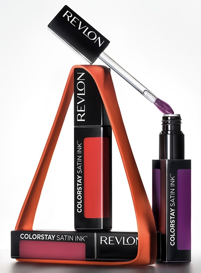 Three tubes of liquid lipstick in pink, red, and purple shades
