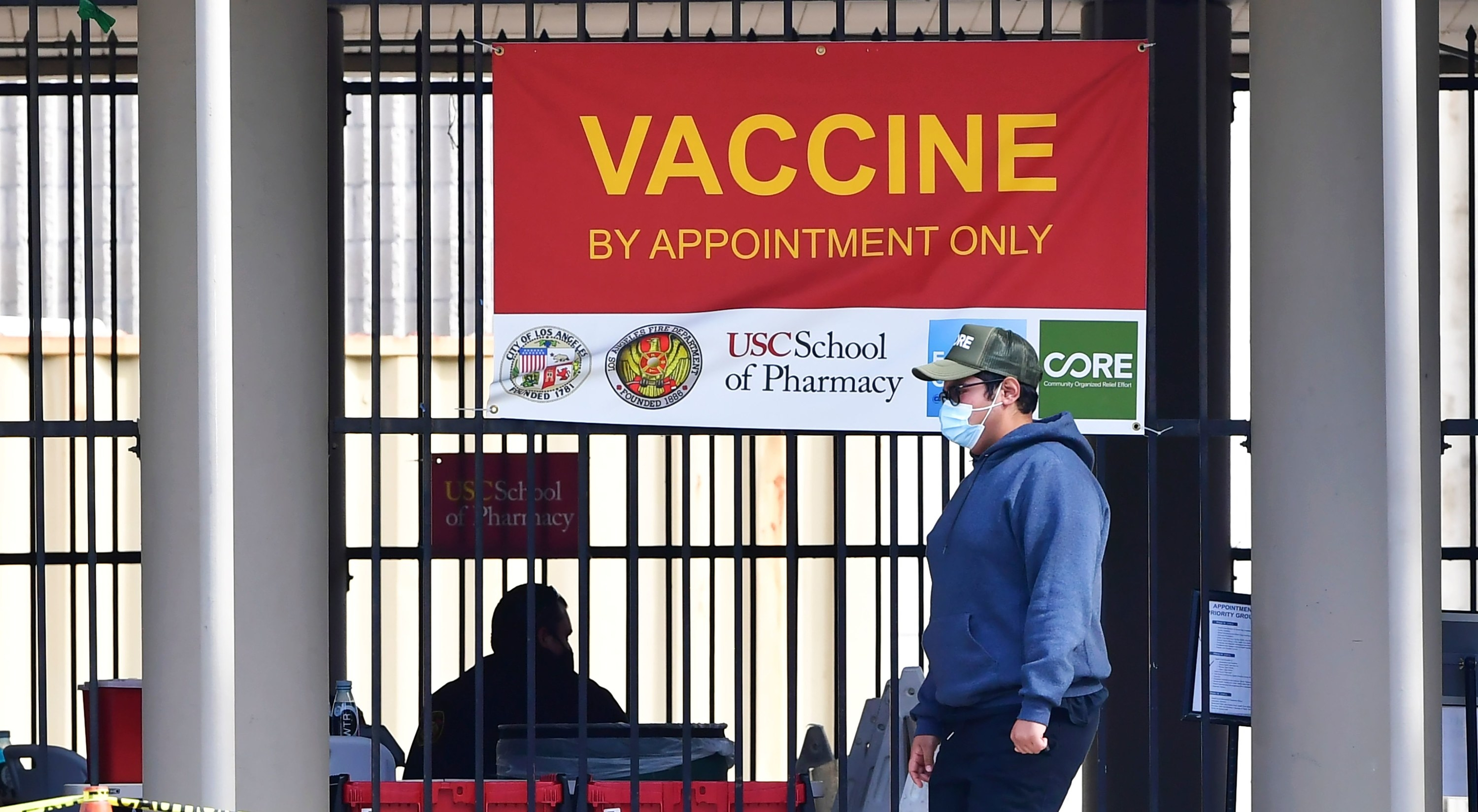 "A sign reading ""vaccine by appointment only"" hangs on a gate"