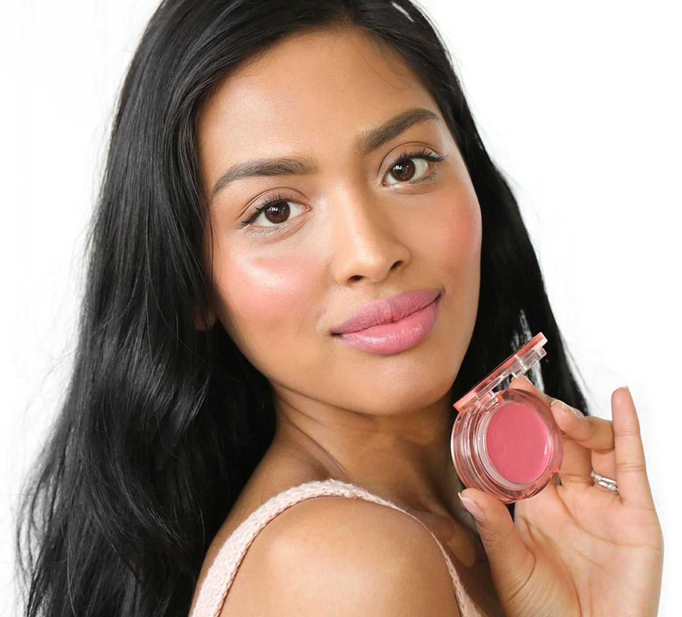 person holding the product with it on her cheeks and lips too