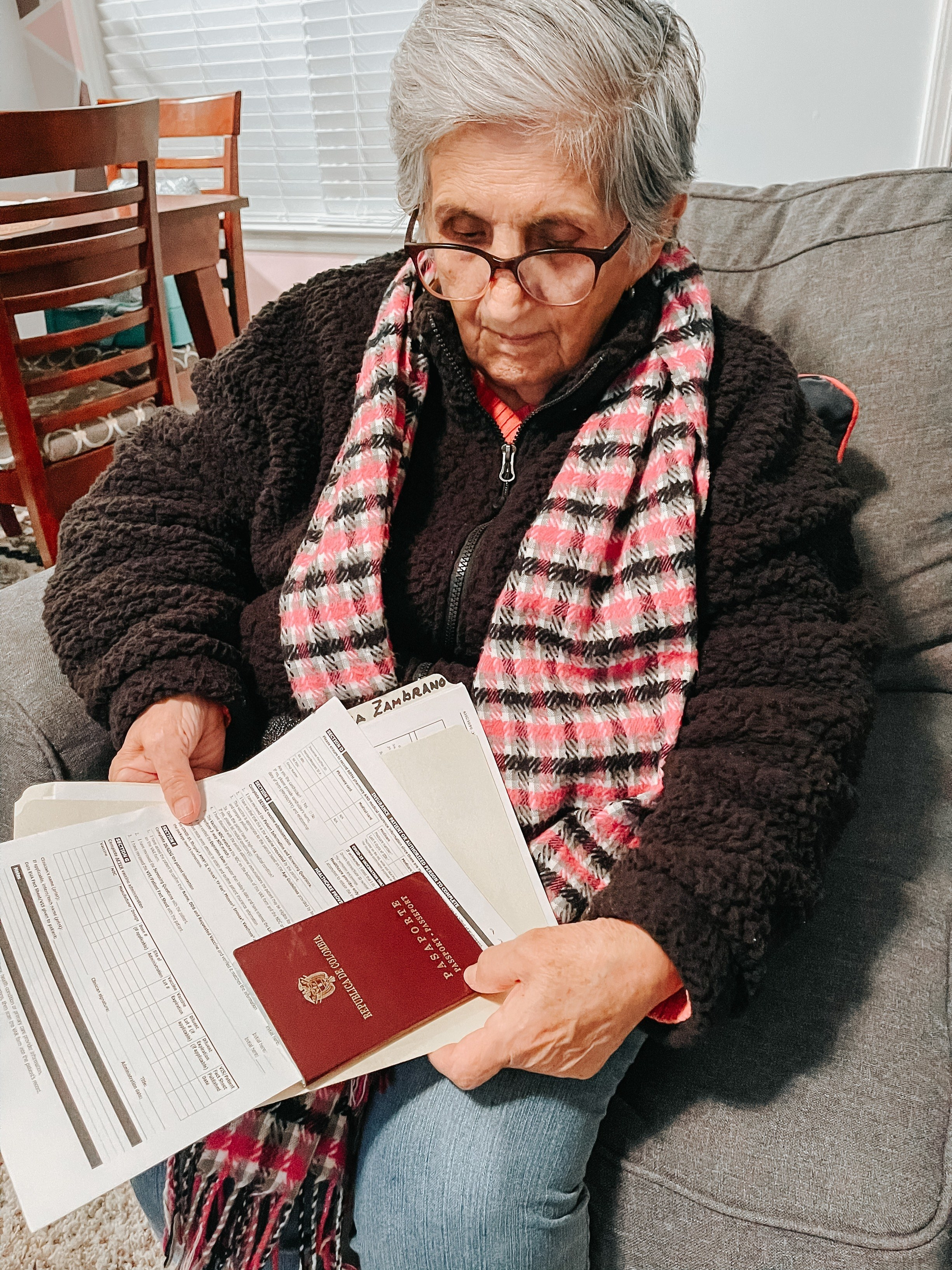 An older woman holds a passport and other documents in her hands