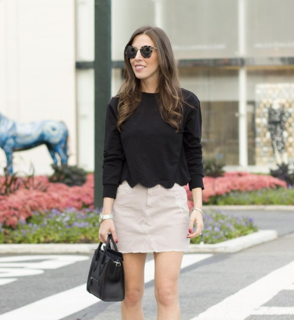 A person wearing a khaki skirt and a black scalloped hem top