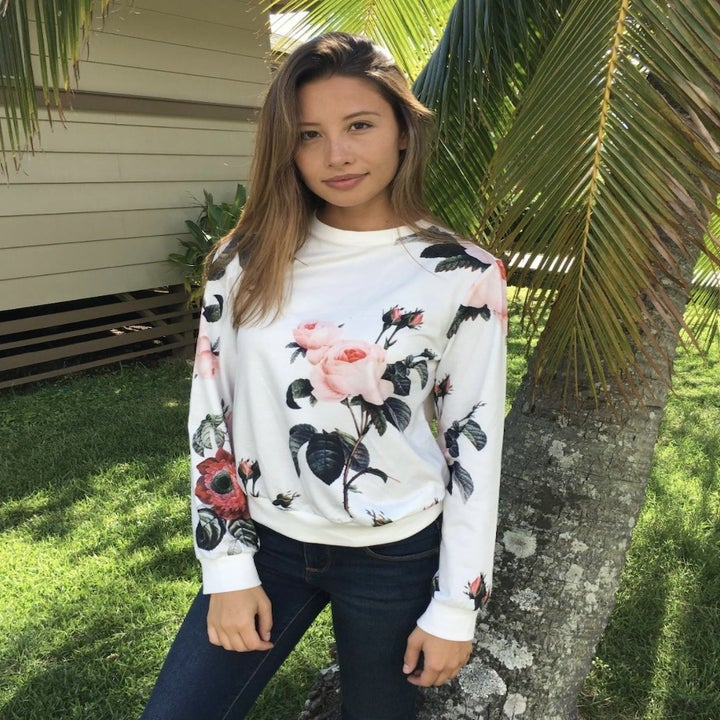 Person is wearing a white sweater with a floral design on it