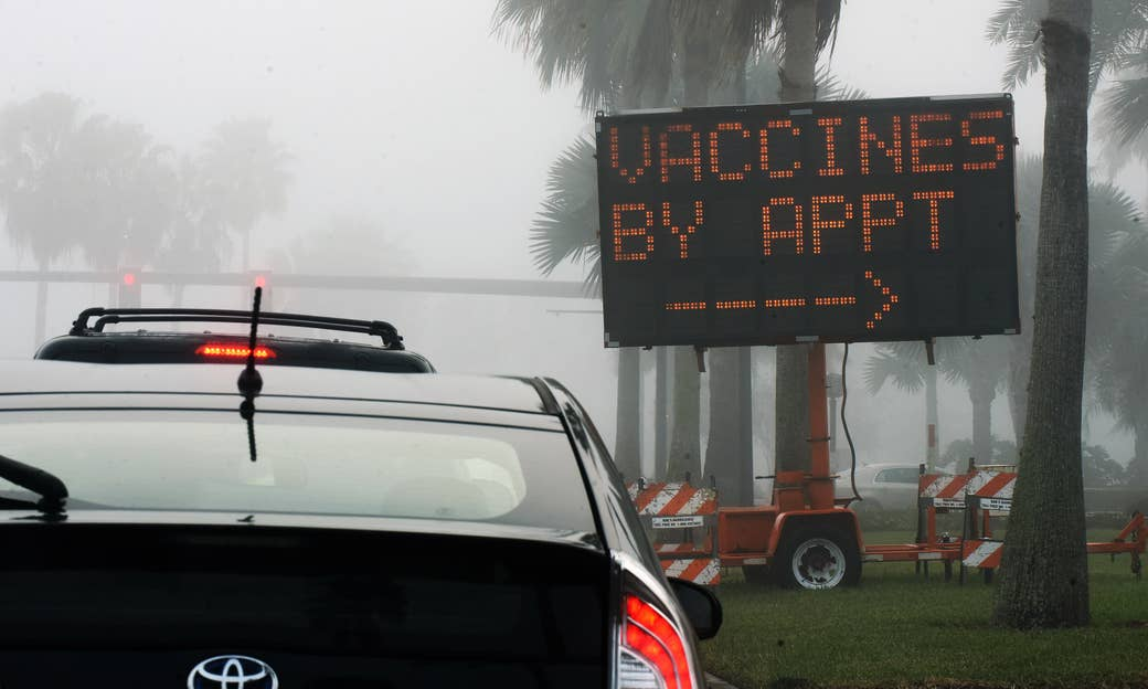 "A large roadside sign reads ""Vaccines by appointment"" with an arrow pointing to the left as cars line up"