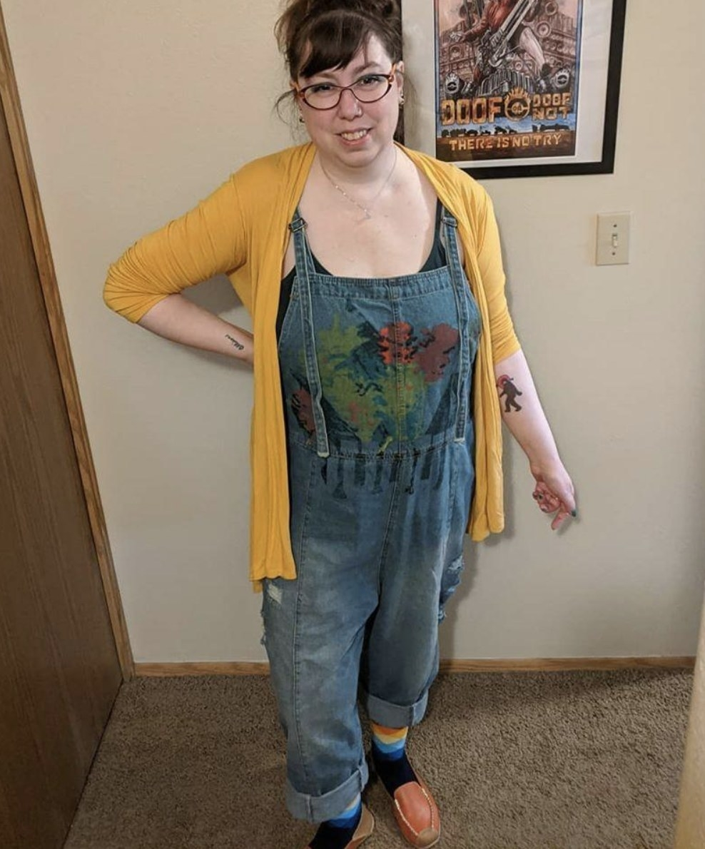 A person wearing hand-painted blue denim overalls, a yellow cardigan, and a green tank top
