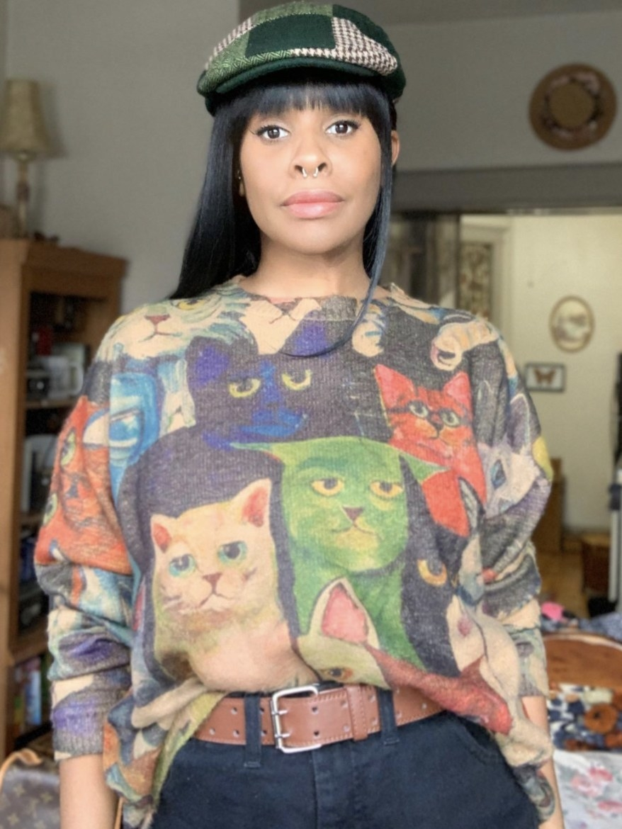 Person is wearing a graphic sweater with various cats on it