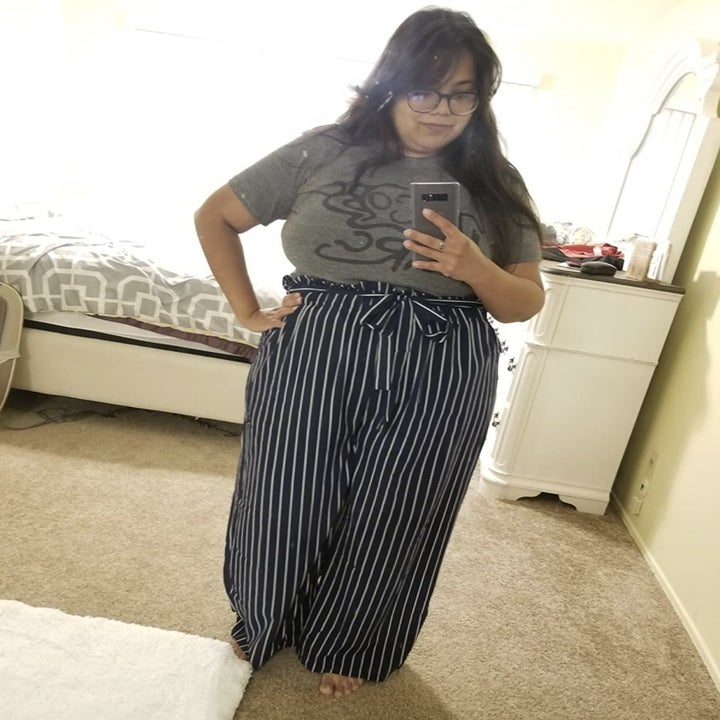 A person wearing a grey top and black and white striped paper bag pants