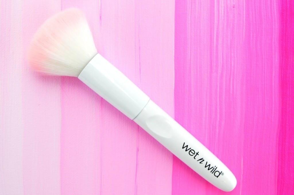 A white powder makeup brush on a pink backdrop