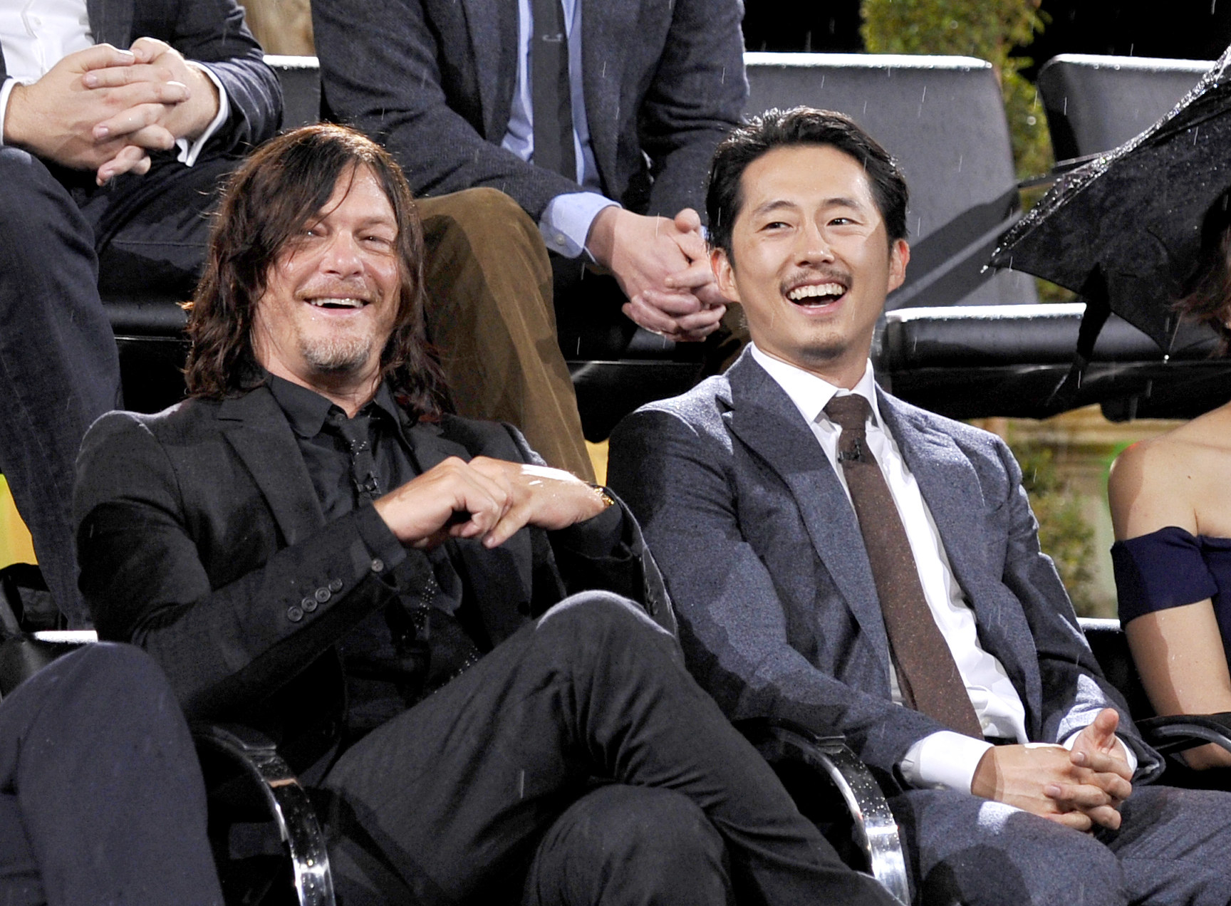 Steven Yeun and Norman Reedus sitting together at a panel