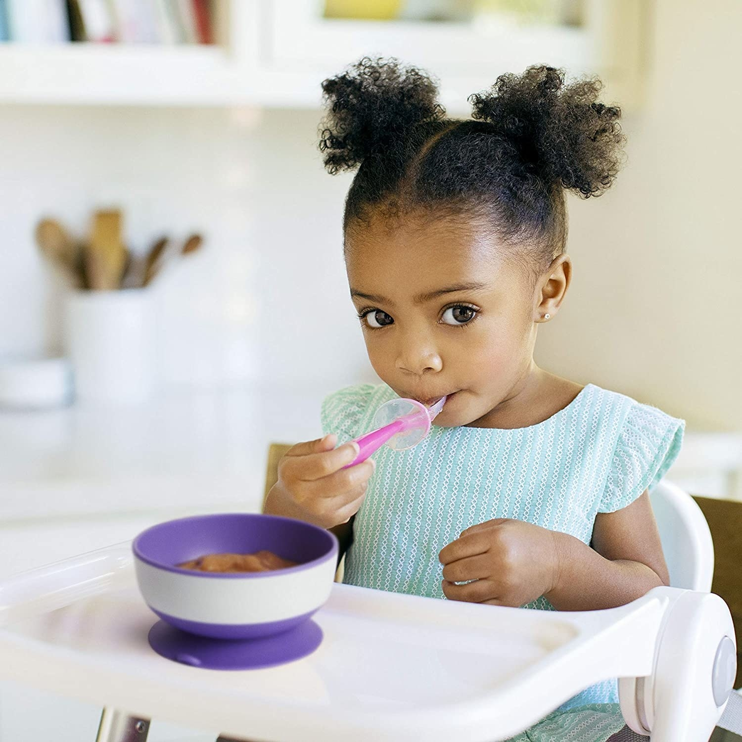 A cute kid eating from the bowl that's suction-cupped to their high chair tray