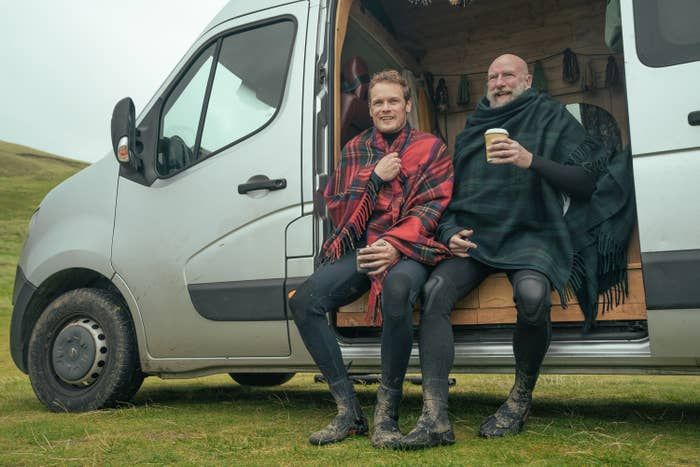 Sam and Graham wrapped in blankets as they sit in their van