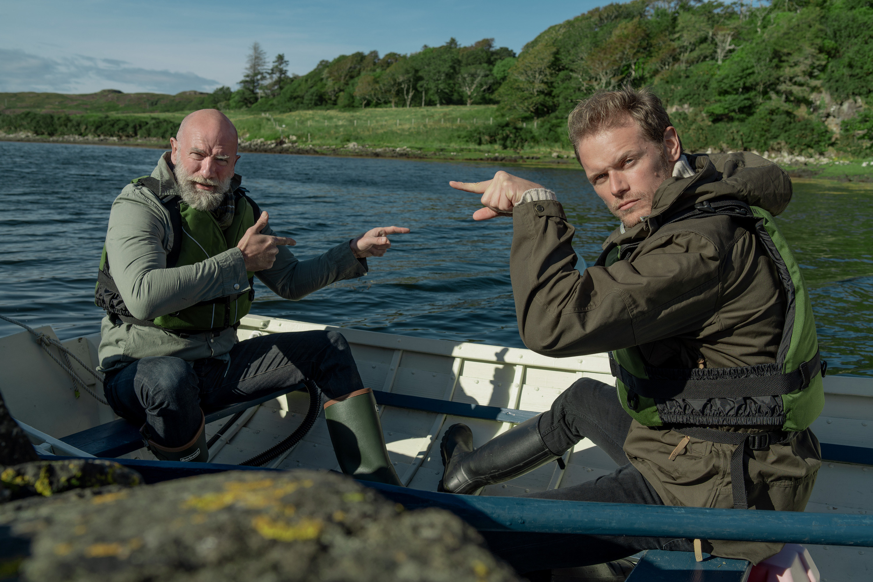 Sam and Graham pointing at one another while sitting in a boat