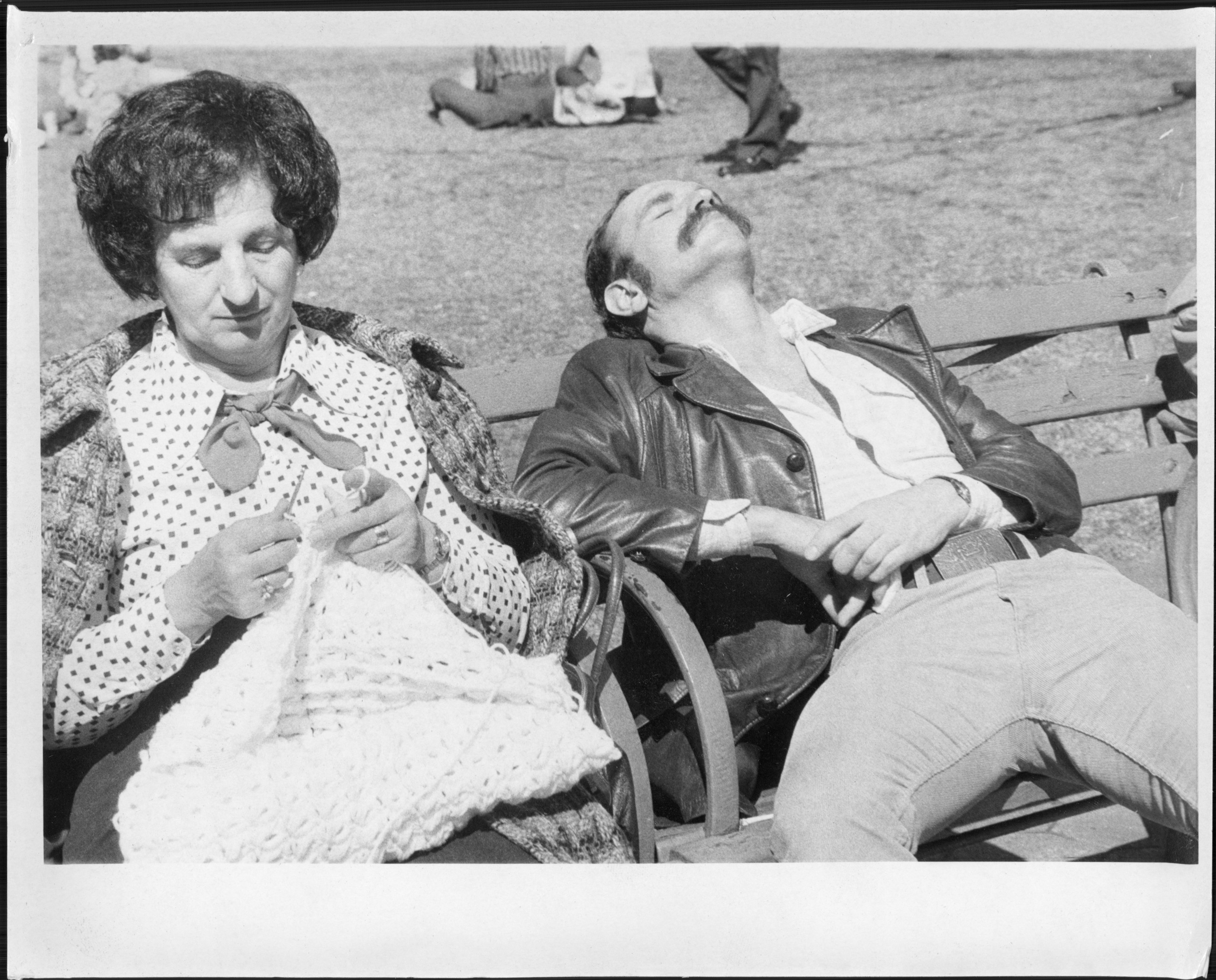 A woman knits on a park bench while a man naps next to her