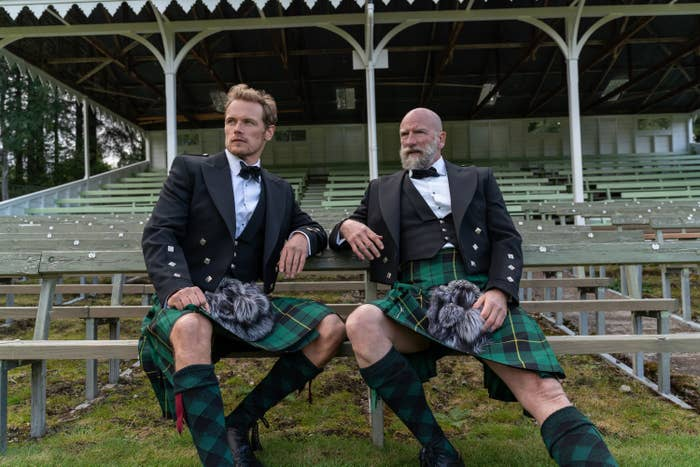 Sam and Graham rocking kilts as they sit on bleachers