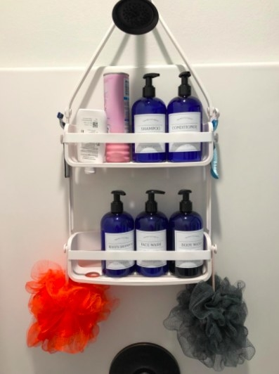 white shower caddy with bottles and loofahs on it
