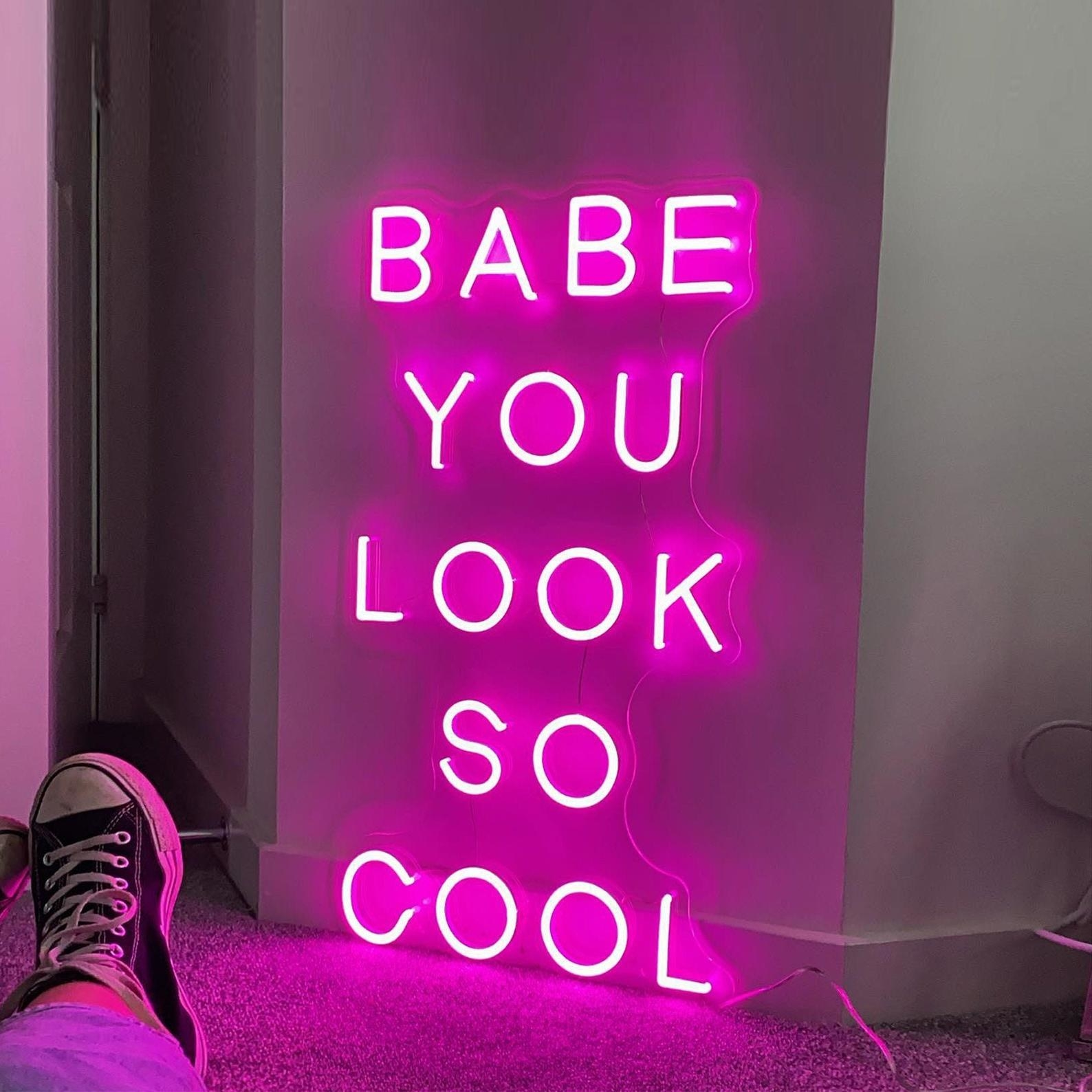 """A neon sign that reads, """"Babe you look so cool."""""""