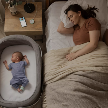 a mom sleeping next to a baby who is in their bassinet with the owlet sock on