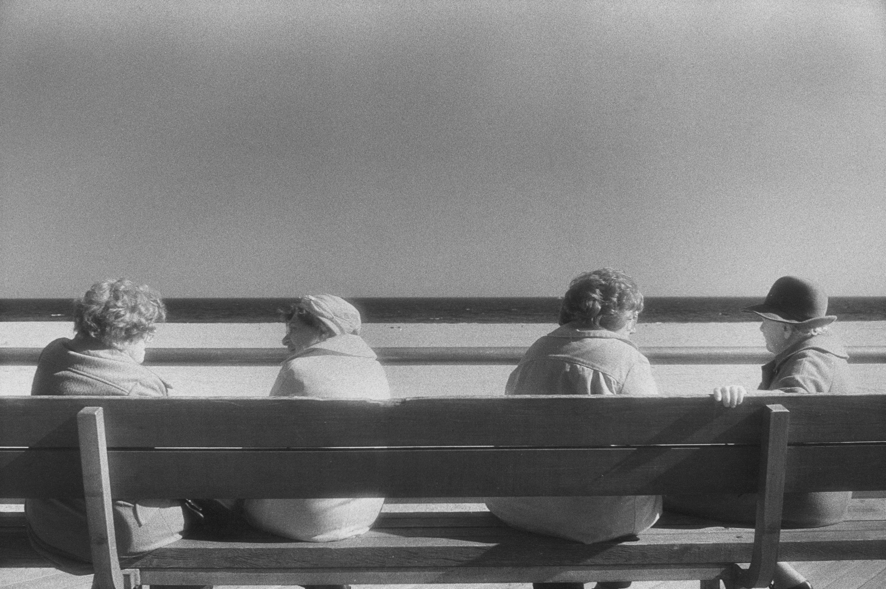 Four older women talking to each other on a bench in front of a beach