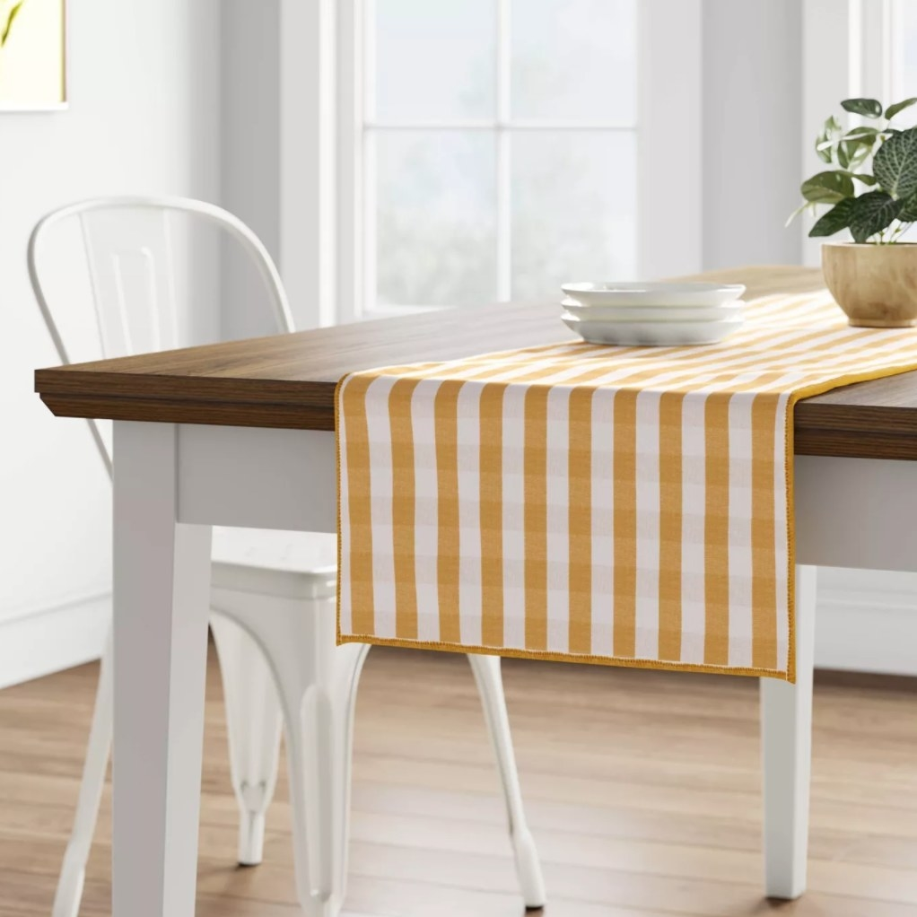 The yellow gingham table runner laid out on a table