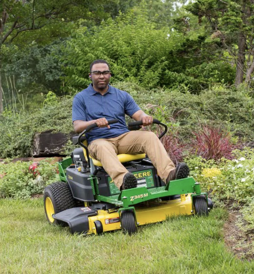 a model riding on the green and yellow lawn mower cutting the grass