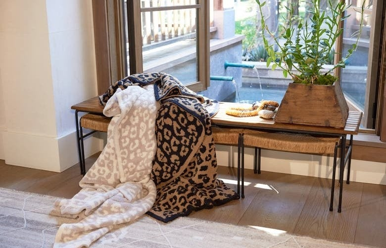Two of the leopard print blankets thrown over a bench