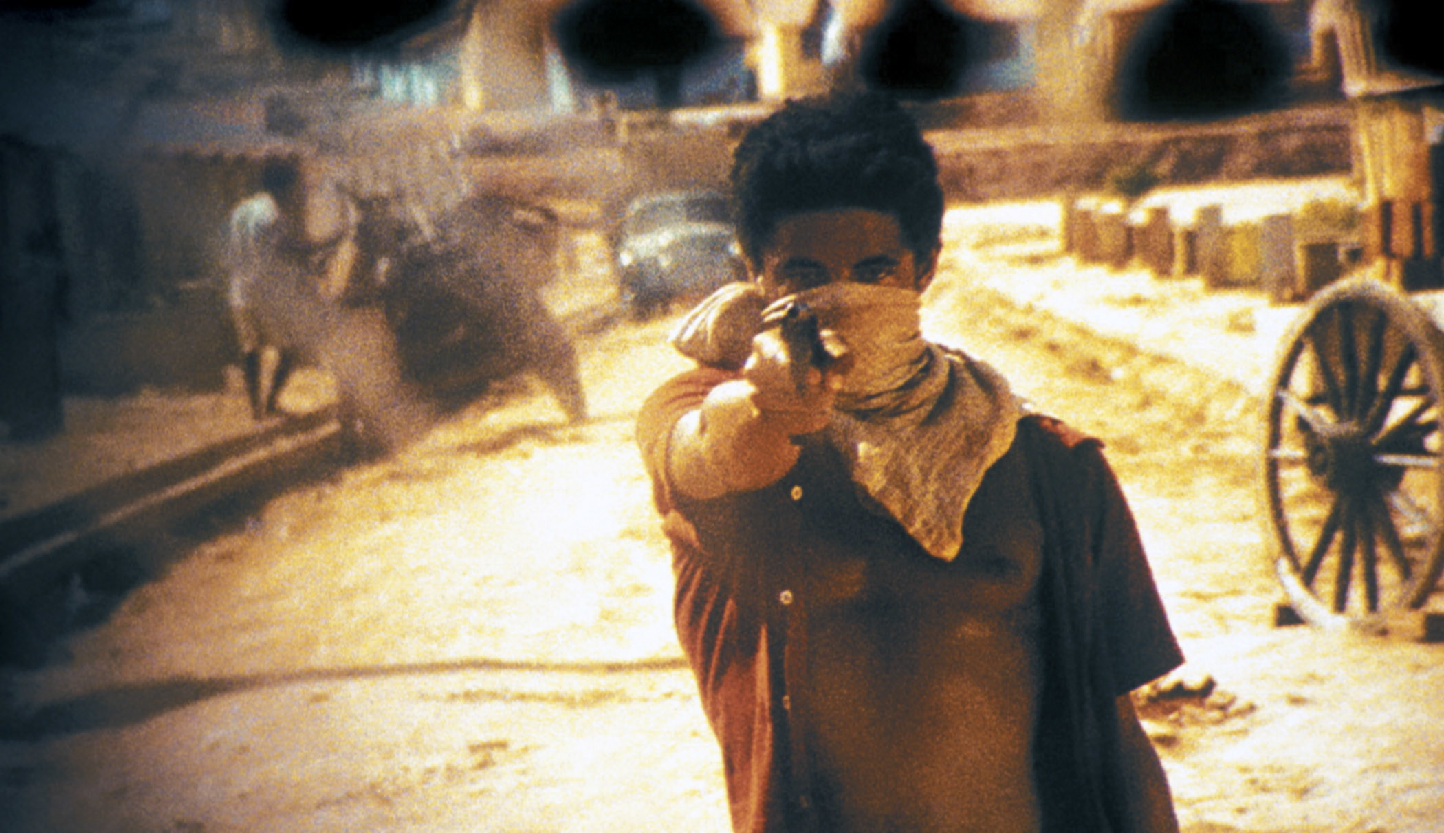 A young boy pointing a gun at the camera