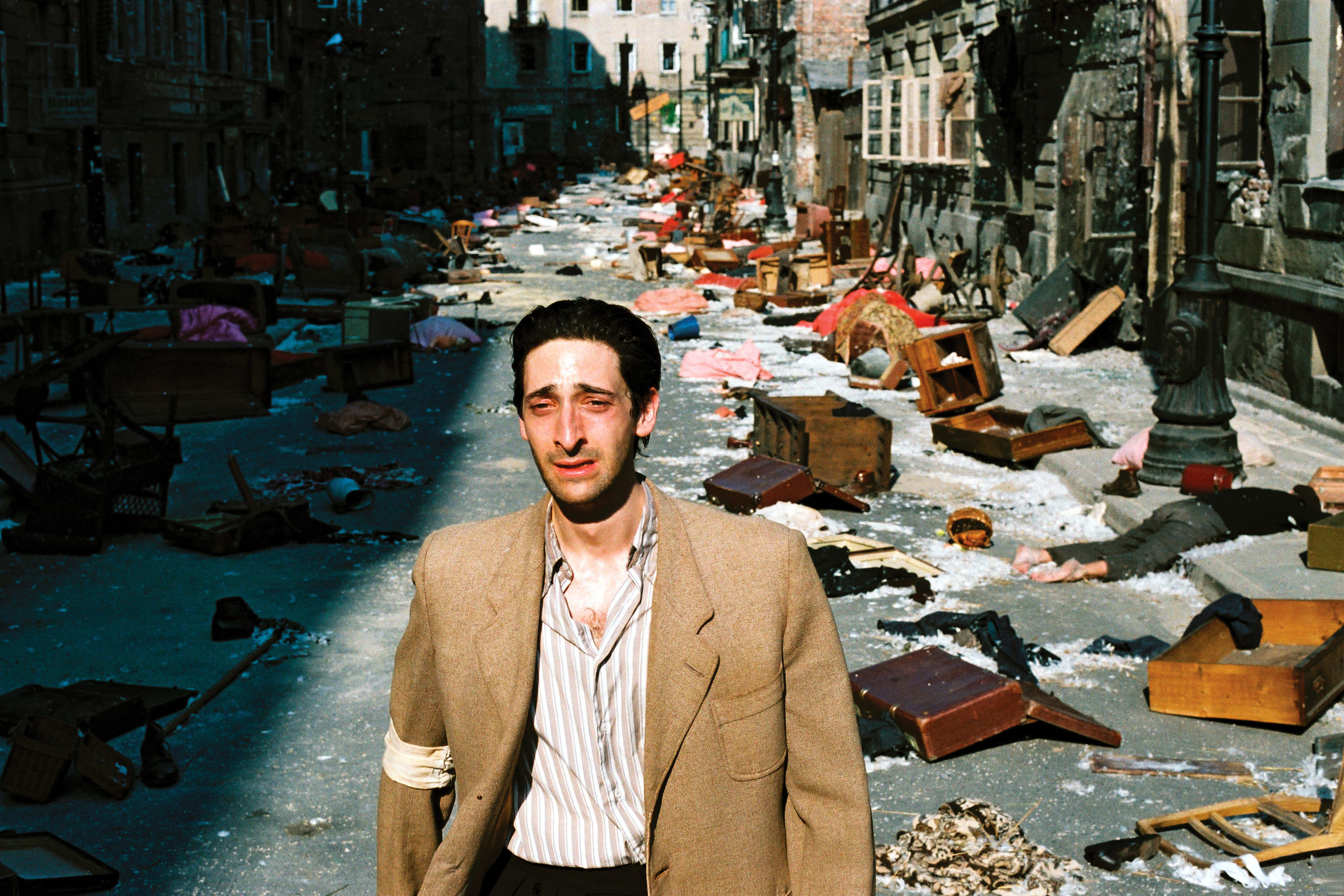 Szpilman crying as he walks away from the chaos and disarray of his neighborhood