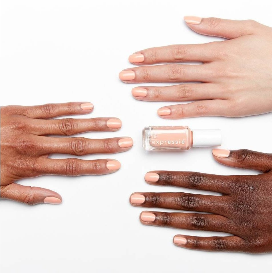 Three hands with different skin tones wearing the same light pink nail polish