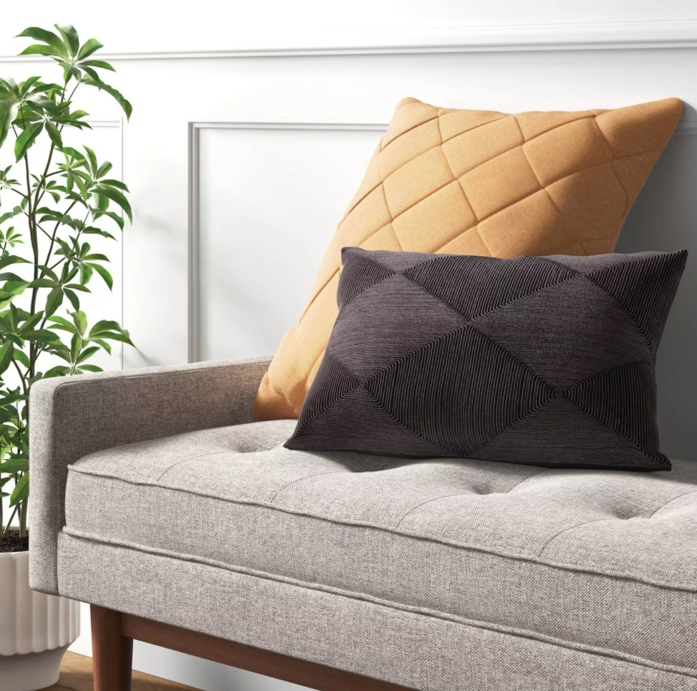 the pillow in mustard on a grey couch