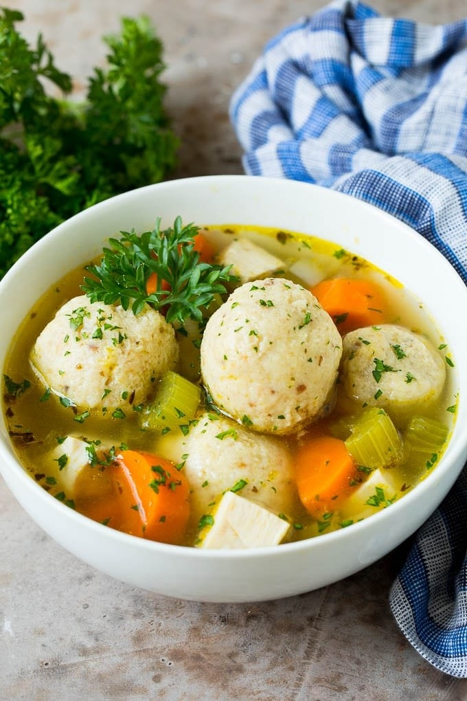 A bowl of matzo ball soup with celery and carrots.