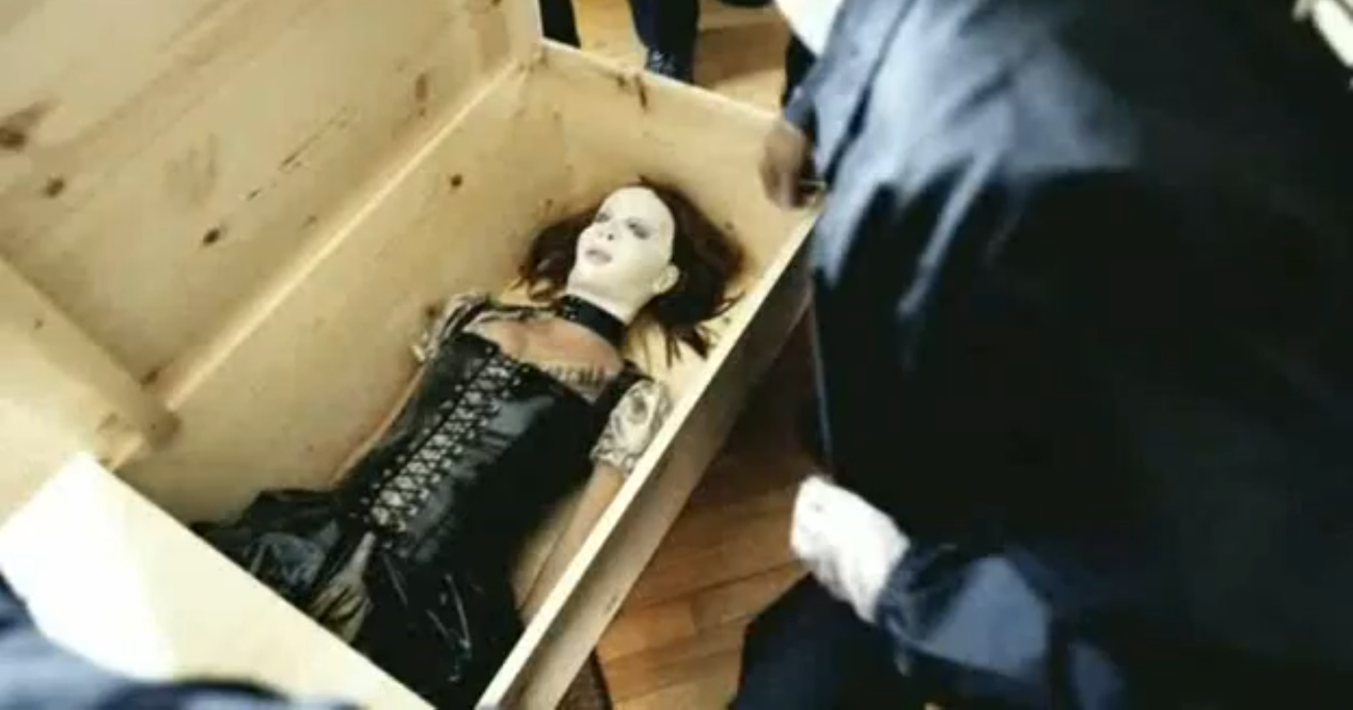 A woman in a mask and leather jacket laying in a box