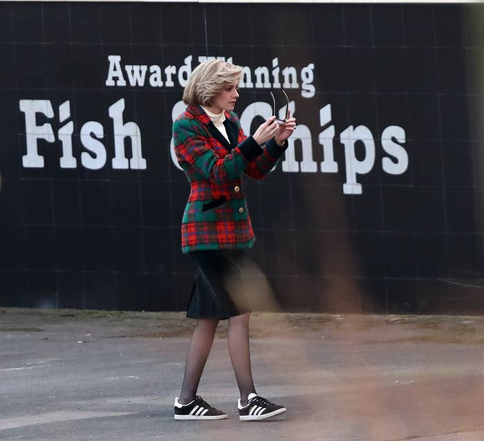 Kristen standing in front of a wall that has the words 'Award Winning Fish & Chips' painted on it
