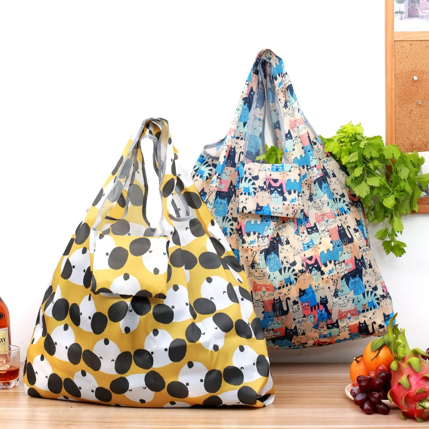 two nylon bag – one yellow with illustrations of a dog in black and white and the other with illustrations of cats in blues, oranges, and reds