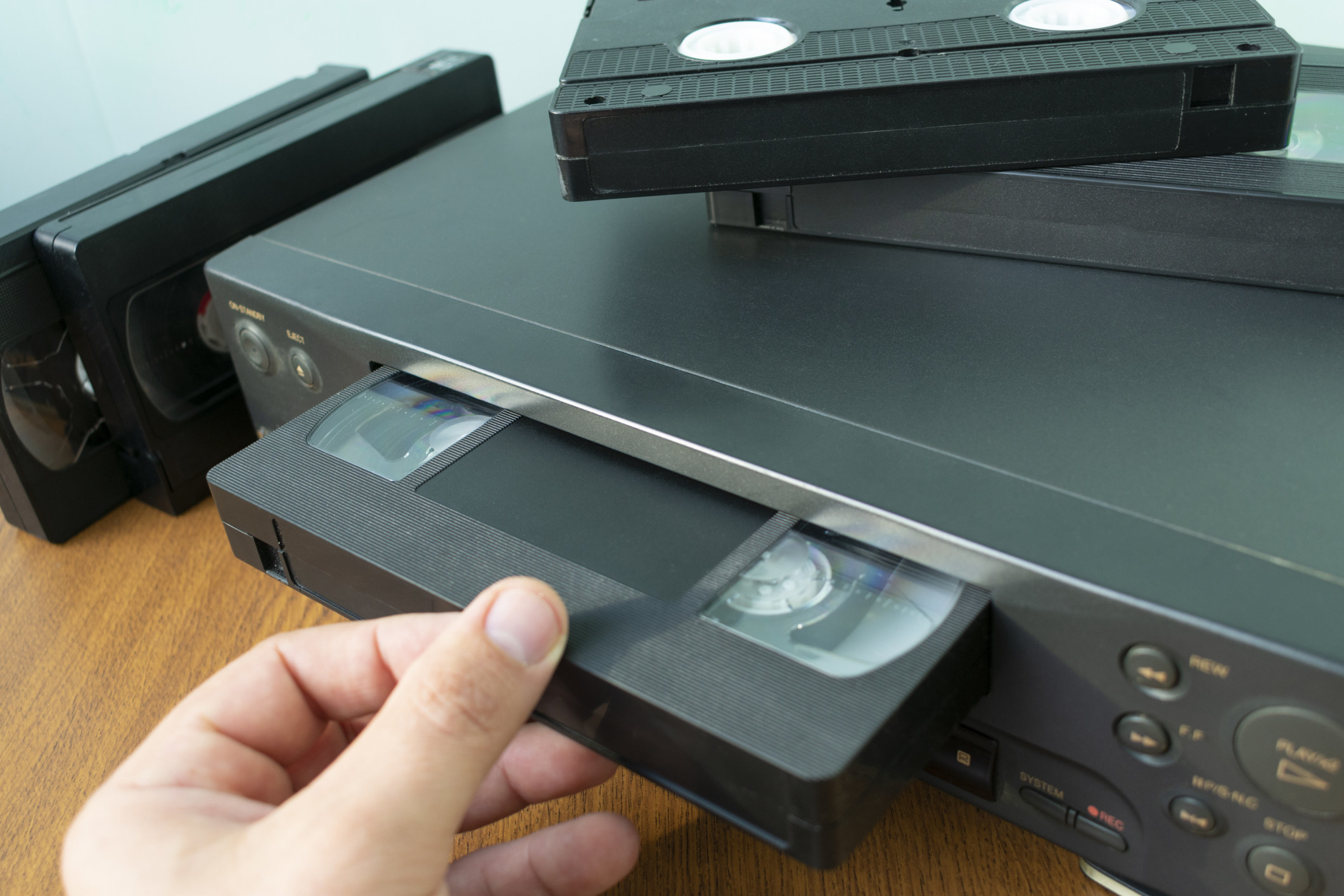 A VHS videocassette being put into a video recorder to watch