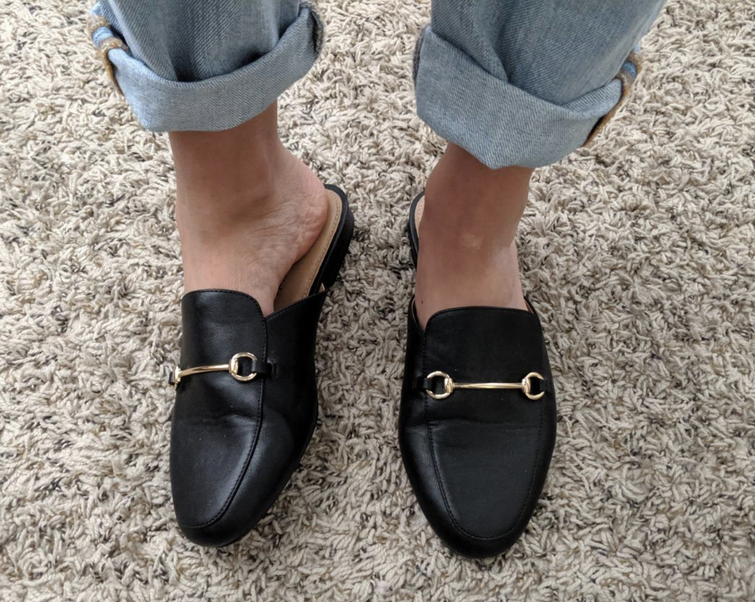 reviewer wearing the black loafers with gold chain design